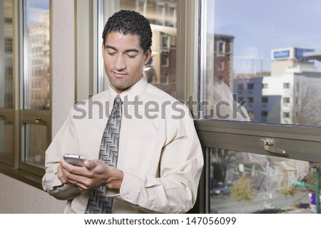 Mixed race businessman text messaging on cell phone - stock photo
