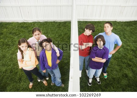 Mixed Race children on opposite sides of fence - stock photo