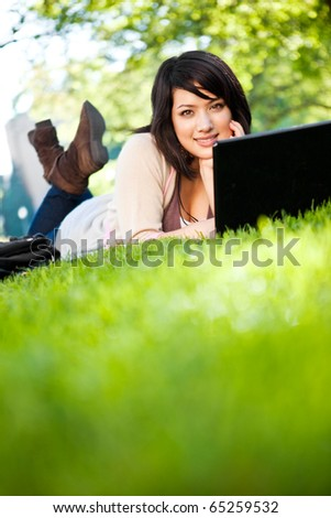 Mixed race college student lying down on the grass working on laptop at campus - stock photo
