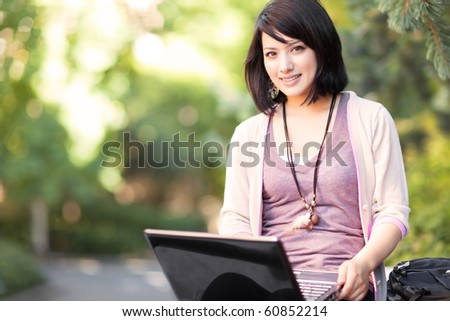 Mixed race college student working on laptop at campus - stock photo