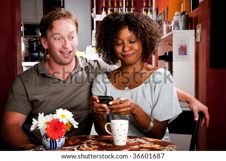 Mixed race Couple in Restaurant with Handheld Phone - stock photo