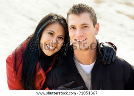 Mixed race couple in winter snow - stock photo