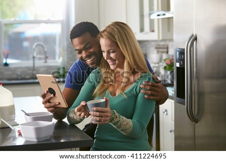 Mixed race couple looking at a tablet computer together in kitchen - stock photo
