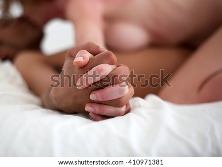 Mixed race couple making love in bed - focus on hand - stock photo