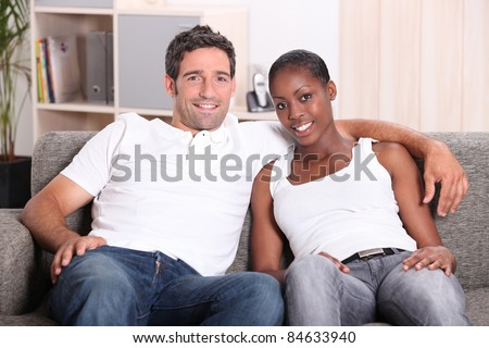 Mixed race couple sat on couch - stock photo