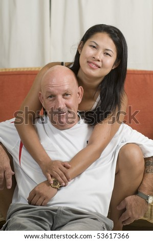 mixed race couple sitting together and smiling - stock photo