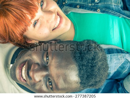 mixed race couple. two teenagers lying on the ground and smiling. fine portrait about diversity - stock photo