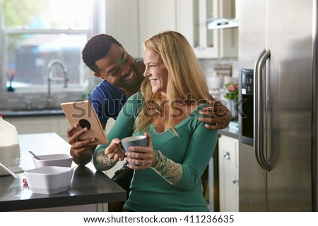 Mixed race couple using a tablet computer look at each other - stock photo
