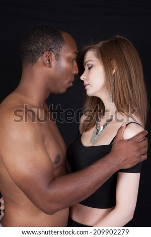 Mixed race couple with a African American man and a Caucasian woman, looking at each other in a romantic mood, he is topless