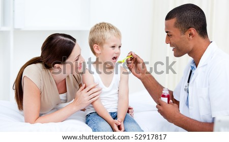 Mixed-race doctor giving some syrup to the little boy at the hospital - stock photo