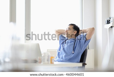Mixed race doctor relaxing at desk