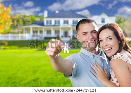 Mixed Race Excited Military Couple In Front of New Home Showing Off Their House Keys. - stock photo