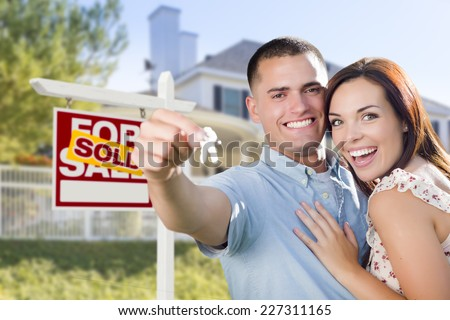 Mixed Race Excited Military Couple In Front of New Home with New House Keys and Sold Real Estate Sign Outside. - stock photo
