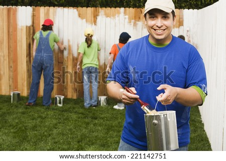 Mixed Race family painting fence - stock photo