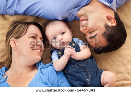 Mixed Race Family Playing Face Up on the Blanket. - stock photo
