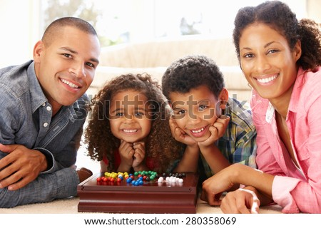 Mixed race family playing solitaire - stock photo