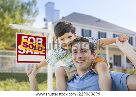 Mixed Race Father and Son Celebrating with a Piggyback in Front of House and Sold Real Estate Sign.