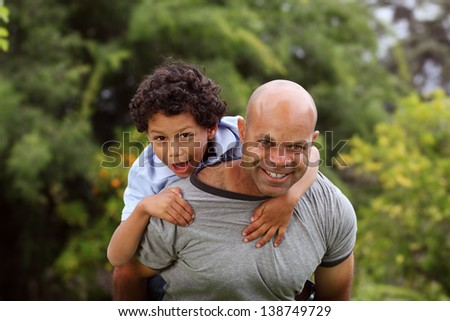 Mixed race father and son playing in the back garden - stock photo