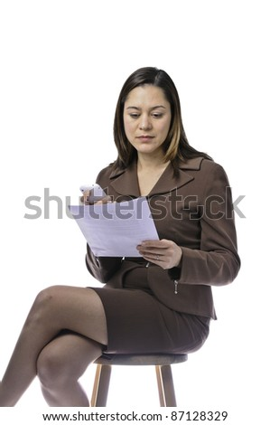 Mixed race female reading  a sheet of paper. She is sitting and holding telephone.This has clipping path - stock photo