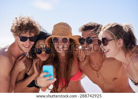 Mixed race friends smiling while taking funny selfie wearing bright colored bikinis and sunglasses