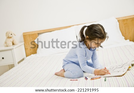 Mixed Race girl coloring on bed - stock photo