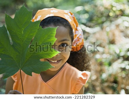 Mixed Race girl holding leaf in front of face - stock photo