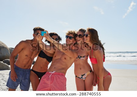 Mixed race group of attractive friends taking happy selfie with mobile phone smiling have healthy toned beach bodies