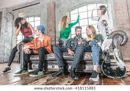 Mixed race group of teenagers having fun on the couch - stock photo