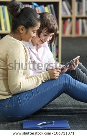 Mixed race group of two female girl students using tablet computer in a college library - stock photo