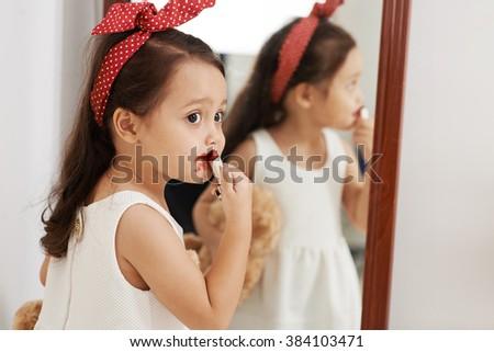 Mixed-race little girl applying red lipstick - stock photo