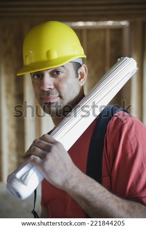 Mixed Race male construction worker holding blueprints