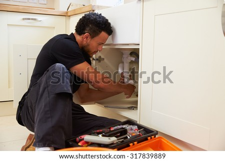 Mixed race plumber fixing the kitchen sink in a home - stock photo