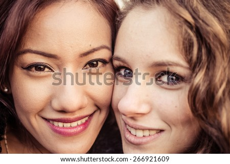 mixed race portrait. asian  and caucasian girl posing together and looking in camera