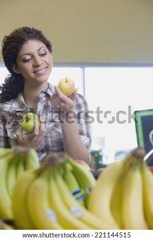 Mixed Race woman choosing apples at grocery store - stock photo