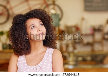 Mixed race woman in a coffee shop looking away thoughtfully and daydreaming - stock photo