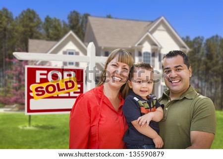 Mixed Race Young Family in Front of Sold Home For Sale Real Estate Sign and New House. - stock photo