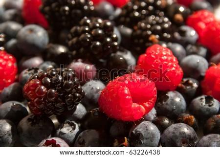 Mixed raspberries, blueberries and blackberries background - stock photo