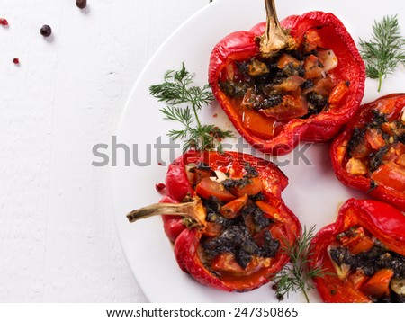 Mixed rice with roasted bell peppers stuffed with pesto and tomato on white plate. White wooden background. - stock photo