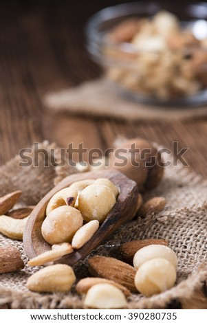 Mixed roasted and salted nuts (selective focus) on an old wooden table
