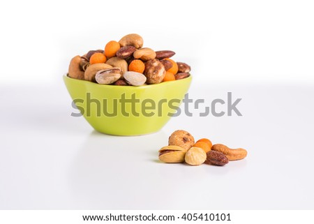 Mixed Roasted nuts, pistachios and cashews in green bowl. - stock photo
