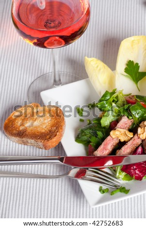 mixed salad on a white plate with a glass of rose - stock photo