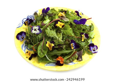 Mixed salad with flowers on a yellow plate isolated over white - stock photo