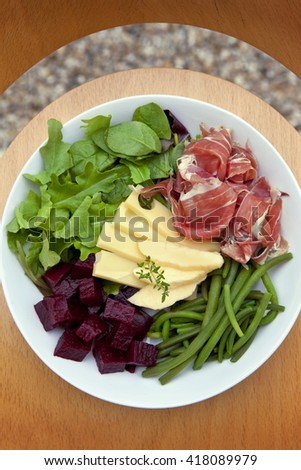 Mixed salad with ham, cheese, beet and beans on a plate - stock photo