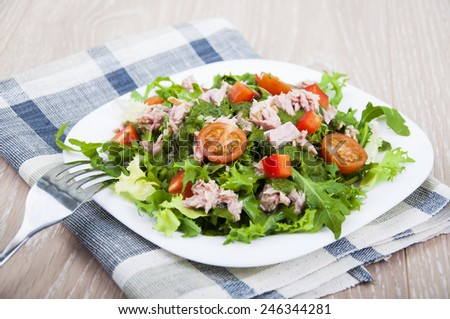 Mixed salad with tuna and tomatoes on a wooden background - stock photo