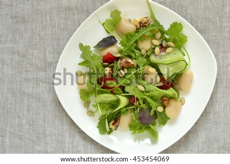 Mixed salad with white beans, greens, cucumbers and sweet peppers, top view