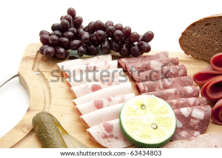 Mixed sausage plate with grapes - stock photo