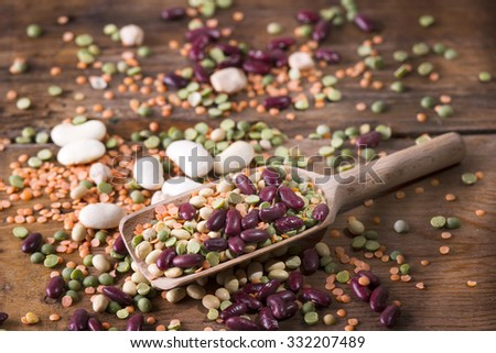 Mixed seed legumes in a spoon on old wooden table - stock photo
