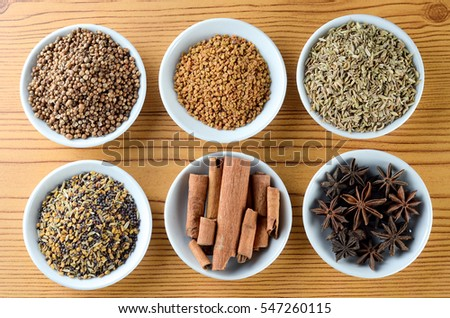 Mixed spice anise, aniseed, cinnamon, fenugreek in bowl over wooden background