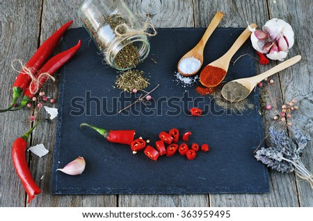 Mixed spices and Condiments  on  the stone, slate and wooden background. Hot peppers and garlic,. Salt, red pepper. black pepper, a bunch of lavender,  - stock photo