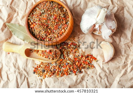 Mixed spices in wooden scoop and bowl on parchment background - stock photo